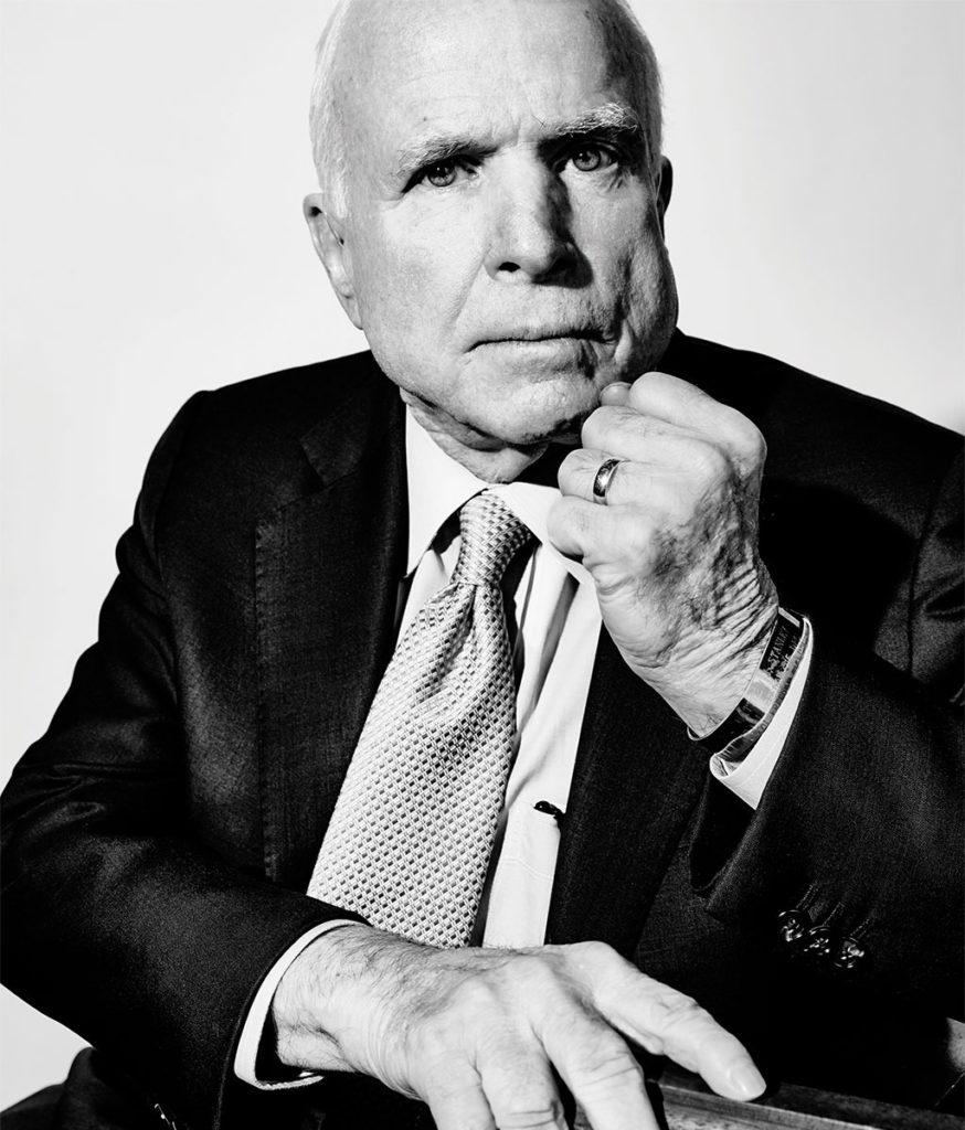 zwart wit foto van oud presidentskandidaat john mccain. hij kijkt  pijnzend de camera in en heeft een zwart pak aan