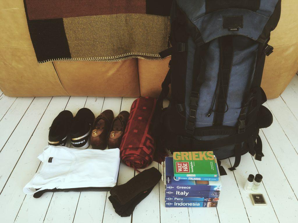 foto van vakantiespullen die gepakt zijn je ziet een backpack, schoen, reisboekjes, kleren etc.
