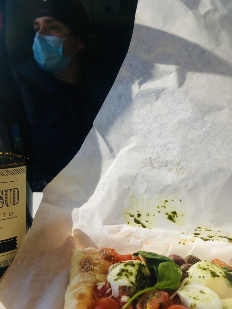 Foto van de pizza die nicolas heeft besteld in de trein in italie. Op de achtergrond zie je een persoon met een mondkapje op