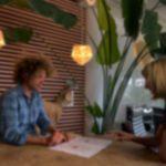 Fitch psycholoog zit met een coachee aan tafel in de fitch ruimte hij legt een fitch rapportage uit en er staat een grote groene plant op de achtergrond