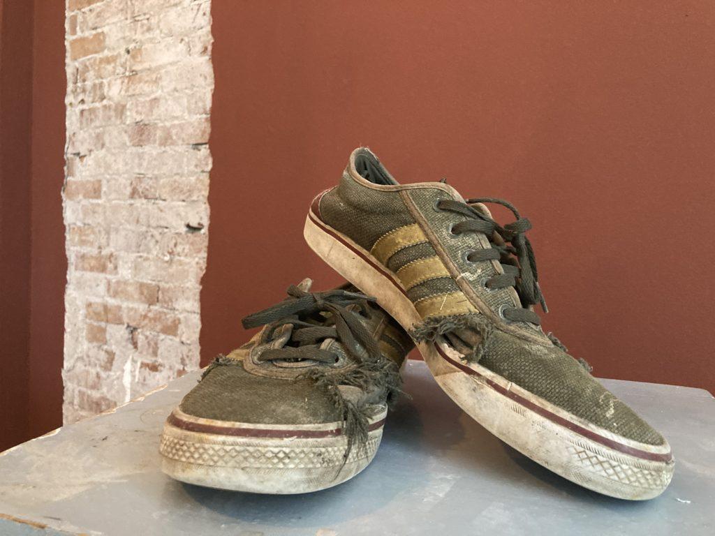 een paar afgetrapte schoenen van fitch psycholoog Nicolas Pop staan voor een rode muur